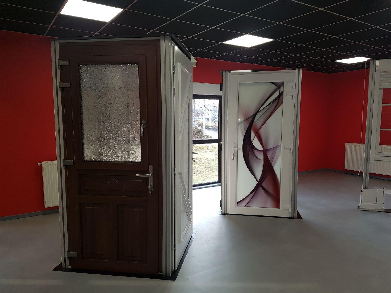 Showroom présent les portes en PVC, en bois et en aluminium d'un menuisier expert qualifié RGE